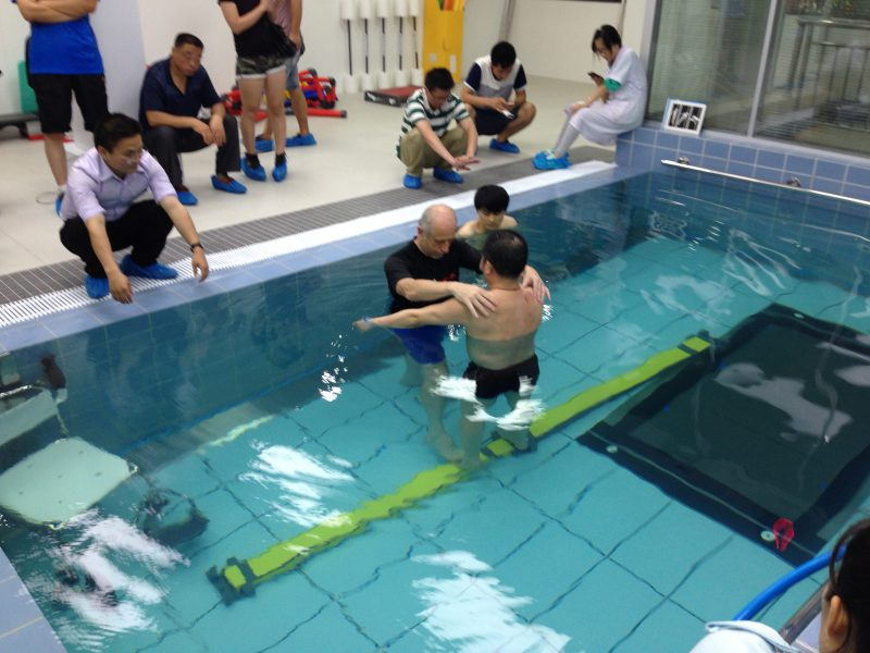 Therapist with individual in pool with obstacle course