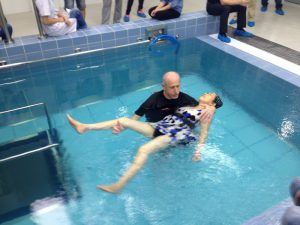 Passive practice of hydrotherapy, therapist with individual in water